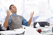 stock photo of throw up  - Happy businessman sitting at desk - JPG
