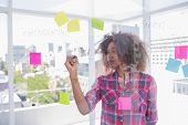 Woman with afro drawing on flowchart with marker in bright office