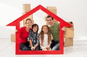 Family with kids portrait in their new home - with cardboard boxes and house shaped frame