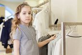 Cute girl tries on a dress in a store childrens clothes