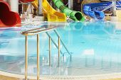 Metal railings, pool and multi-colored water slides in indoor aquapark.