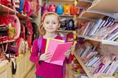 Little girl stands in school department of store with backpack on shoulders, holding several noteboo
