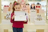 Little girl stands and holds open shoe box in shoe store