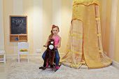 Portrait of little girl on hobbyhorse in playroom