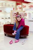 Niña trata de zapato nuevo en tienda