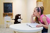 Little girl dreams propping chin sitting in big armchair and viewing book in playroom