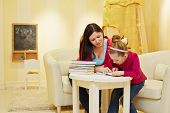 Mother and daughter read book, sitting at table in armchair in playroom