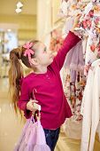 Little girl takes off hangers with dresses from stand in clothing store