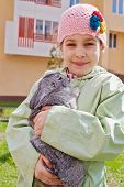 Portrait of smiling little girl in greenish jacket and knitted hat that holds rabbit in her hands