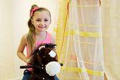 Half-length portrait of little girl on hobbyhorse