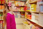 Little girl wonderingly looks on abundance of board games in book department in store