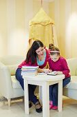 Mother and daughter read book, sitting at table in playroom