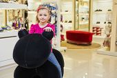 Little girl sits on big stuffed toy in clothing store