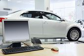 Computer stands on table and new white car stands in office of shop selling cars.
