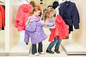 Two girls choose clothes in a store childrens clothes