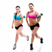 fitness girls, portrait of sport young women with perfect bodies doing exercise with dumbbells, studio shot over white
