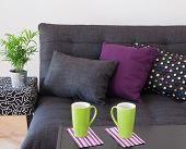 Sofa With Bright Cushions And Green Cups On A Table