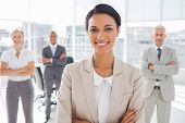 Attractive businesswoman with arms crossed standing in front of colleagues