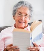Retired woman reading a book at home and smiling