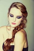 stock photo of gothic hair  - beautiful young woman with blond red hair in fishtail braid and dramatic eye makeup - JPG