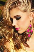 closeup of blond woman with long wet curly hair wearing pink lipstick and gold and pink neon earrings in summer sun