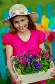 Gardening, planting - lovely girl with petunia flowers in the garden