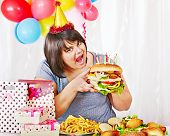 Woman eating hamburger at birthday. Isolated.