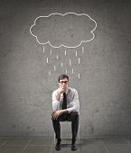 pensive businessman sitting on a chair with a rain cloud above him