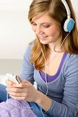Pretty teenage girl listening to music using headphones