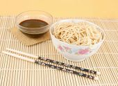 stock photo of lo mein  - delicious chinese lo mein noodles and a bowl of soya sauce on a bamboo place mat with chopsticks - JPG