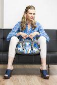 woman wearing denim clogs with a handbag sitting on sofa