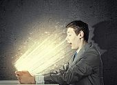 Young businessman looking surprised into tablet pc. Net and communication