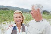 Portrait of a happy senior man embracing woman at the beach