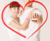 couple, pregnancy and love concept - close up of woman and man hands with pregnancy test