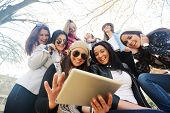Happy teen girls having good fun time outdoors using tablet for reading in park