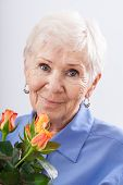 image of grandma  - A closeup of a grandma holding a birthday bunch of roses - JPG