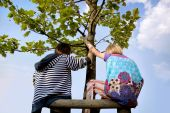 A Boy And A Girl In Bright Clothes On A Tree.