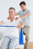 Male therapist massaging a happy mans shoulder in the gym at hospital