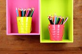 Colorful pencils in pails on shelves on wooden background
