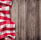 old wooden table with red picnic tablecloth and copyspace