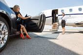 stock photo of jet  - wealthy woman stepping out of car parked in front of private plane and airhostess - JPG