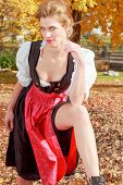 Beautiful woman in a dirndl in an autumn park