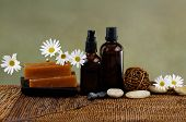 Spa setting with white flower ,soap and stones candle, massage oil,