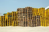 image of wooden pallet  - Stacked up wooden pallets at cargo with blue sky - JPG