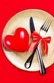 Valentines Day Background With Hearts On A Golden Plate Over Red Cloth. Knife And Fork With Red Tabl