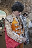 Spainish bullfighter Jose Manuel Montoliu with orange dress and silver putting itself the walk cape
