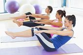 stock photo of stretch  - Side view of class stretching on mats at yoga class in fitness studio - JPG
