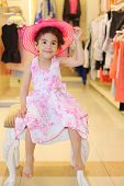 Little barefoot girl in hat sits in children store with clothes for girls.