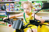 Little cute boy in yellow sits on toy motorcycle in store with toys.