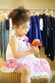 Pretty little girl with red flower sits at pouf in children clothing store.